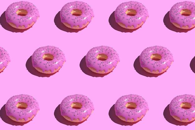 Motif de beignet glacé rose sur pastel.