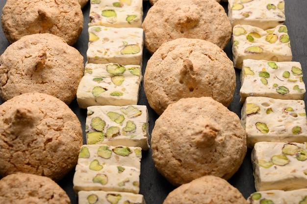 Motif de biscuits aux amandes et nouvas sur fond sombre.