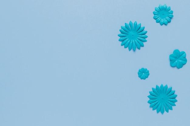 Motif bleu de découpe de fleurs sur une surface unie