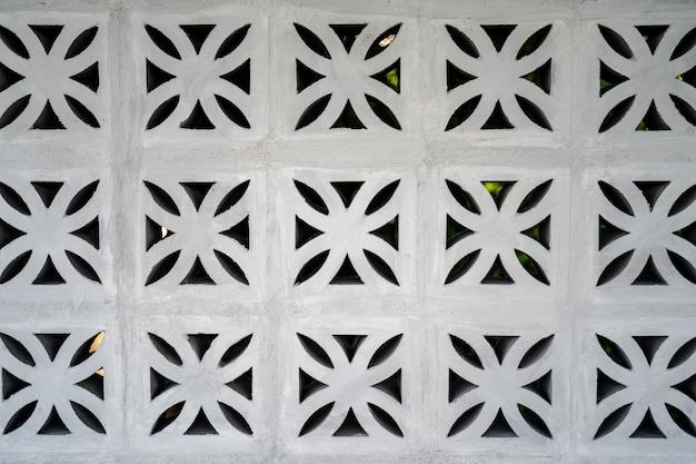 Motif de brique de chantournage de fleurs, fond de cadre perforé, texture sur mur de briques blanches.