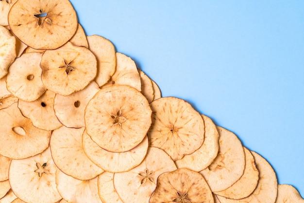 Motif de chips de pomme séchées sur fond bleu avec espace de copie.