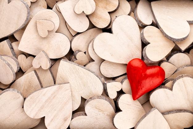 Motif de coeurs en bois, un coeur rouge sur le fond de coeur en bois.