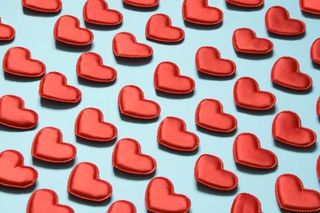 Motif composé de coeurs rouges sur bleu. coeur dans un style isométrique. carte de saint valentin.