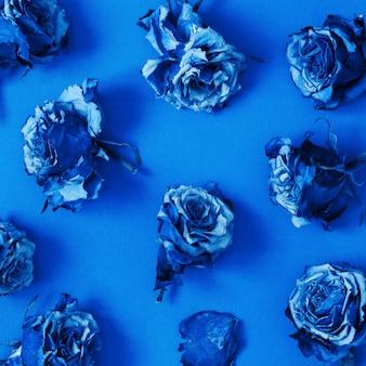 Motif composé de fleurs roses séchées. couleur de l'année 2020 classic blue.