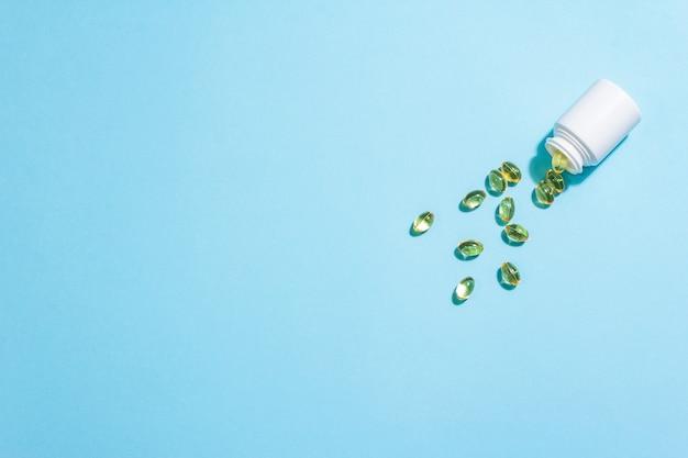 Motif de comprimés omega3 sur un mat bleu.