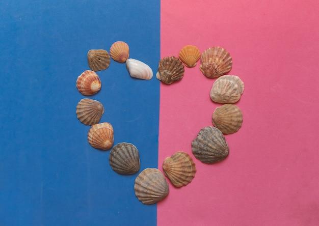 Motif coquillage créatif sur fond rose et bleu pastel. mise à plat d'été.