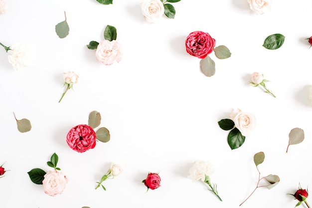 Motif de couronne de cadre rond avec des boutons de fleurs roses rouges et beiges, des branches et des feuilles isolées sur fond blanc. mise à plat, vue de dessus