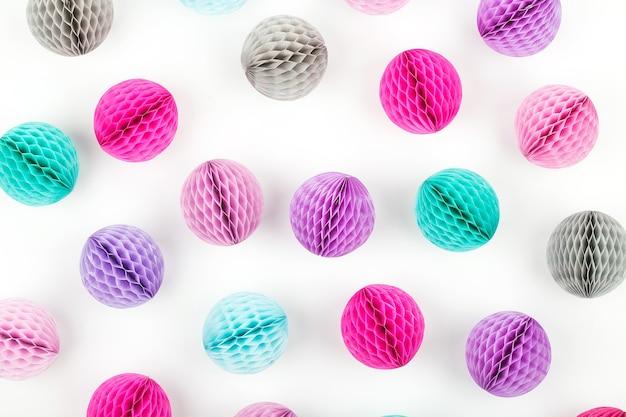 Motif de décorations de boules en nid d'abeille. pompon en papier rose, lilas et turquoise sur fond blanc. mise à plat.