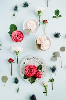 Motif de fleurs composé de roses rouges et beiges sur plaque, branches d'oeillets blancs et d'eucalyptus sur fond bleu pastel pâle. mise à plat, vue de dessus