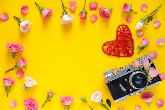 Motif floral de cadre rond en roses roses et beiges, feuilles vertes et appareil photo argentique sur fond jaune. fond de la saint-valentin. mise à plat, vue de dessus.