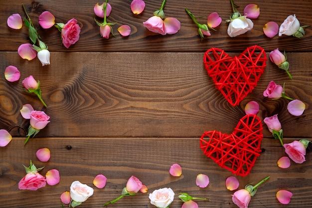 Motif floral composé de roses roses et beiges, feuilles vertes sur fond en bois. fond de la saint-valentin. mise à plat, vue de dessus.