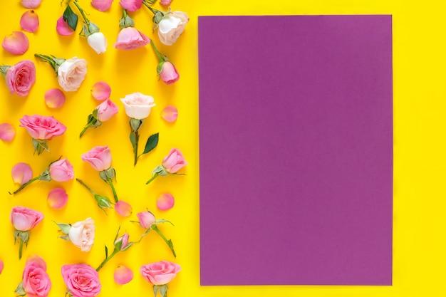 Motif floral composé de roses roses et beiges, feuilles vertes sur fond jaune. fond de la saint-valentin. mise à plat, vue de dessus.