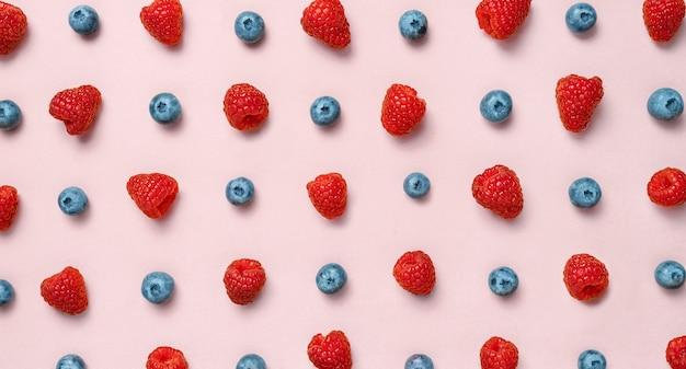 Motif de fruits colorés de framboises et de bleuets sur fond rose. mise à plat. vue de dessus