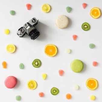 Motif de fruits lumineux colorés avec appareil photo vintage et bonbons sur un mur blanc. mise à plat.