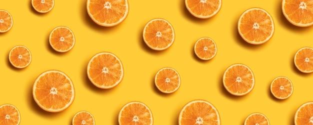 Motif de fruits de tranches d'orange fraîches sur fond jaune.