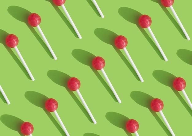 Motif géométrique avec des sucettes chupachups sur fond vert
