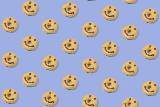 Motif isométrique d'un beignet joyeux et joyeux sur fond bleu pastel. concept de dessert minimal
