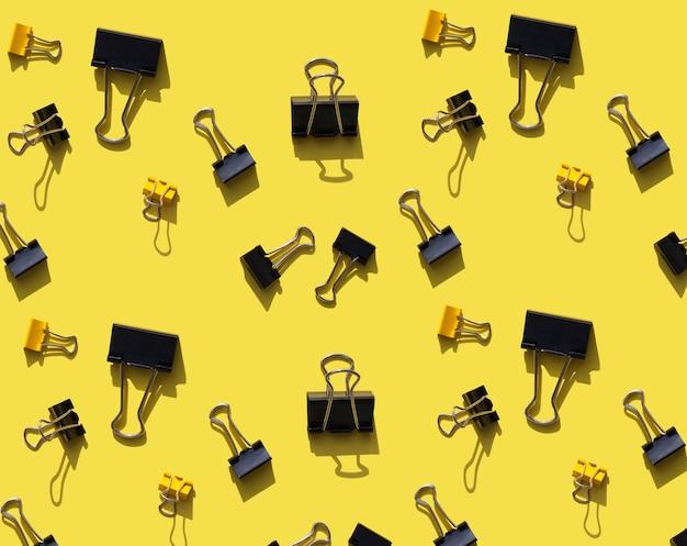 Motif jaune vif avec fournitures de bureau ou scolaires fond graphique avec clips noirs