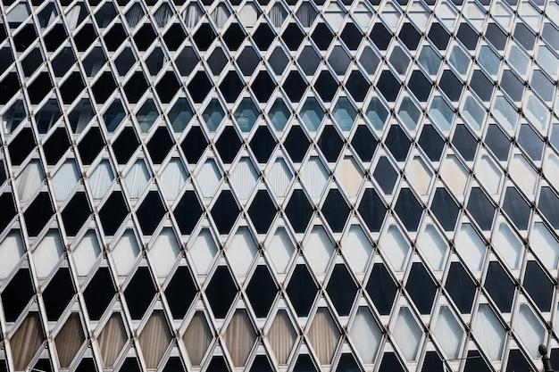Motif losange géométrique sur la façade métallique d'un immeuble au soleil.
