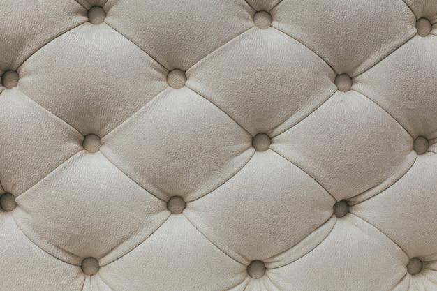 Motif losange textile en velours beige clair avec boutons.
