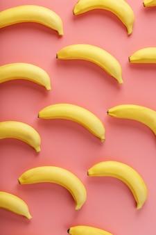 Motif lumineux de bananes jaunes sur fond rose. vue d'en-haut. mise à plat. modèles de fruits