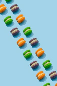 Motif macarons colorés sur fond bleu. desserts français colorés.