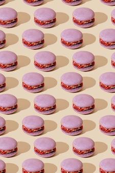 Motif macarons lilas sur fond beige. desserts français colorés.