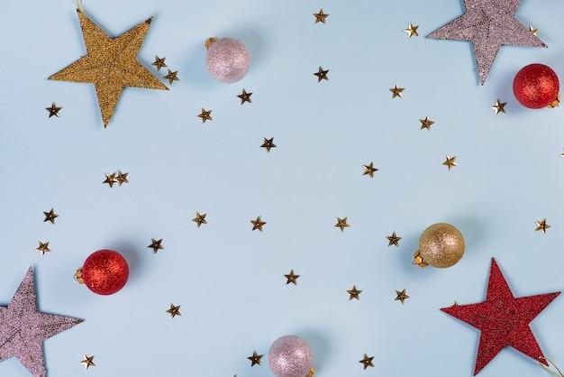 Motif de noël composé de boules d'étoiles dorées, argentées et rouges sur bleu