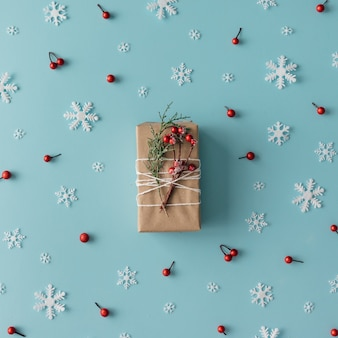 Motif de noël en flocons de neige, baies rouges et boîte-cadeau. concept d'hiver. mise à plat.