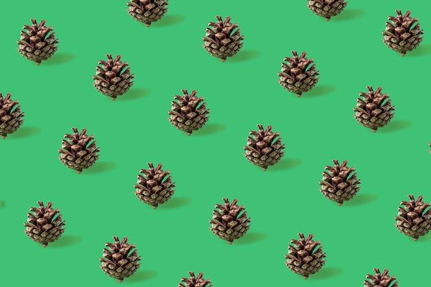 Motif de noël sans couture de pommes de pin sur fond vert
