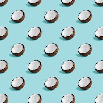 Motif de noix de coco sur fond vert clair. la moitié de la noix de coco dans un style plat minimal