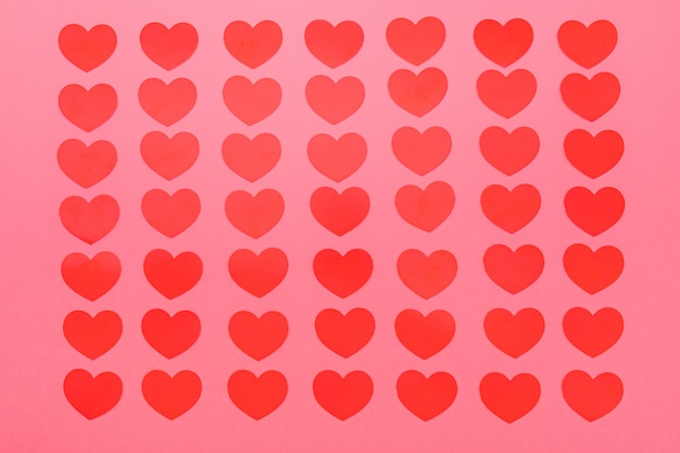 Motif de petits coeurs rouges sur fond rose