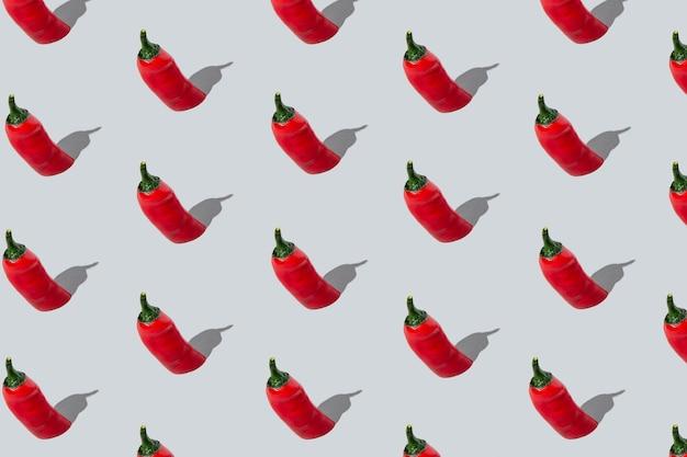 Motif de piments rouges sans couture sur fond gris clair. disposition isométrique.