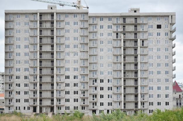 Motif texturé d'un mur de bâtiment résidentiel russe en pierre blanche avec plusieurs fenêtres