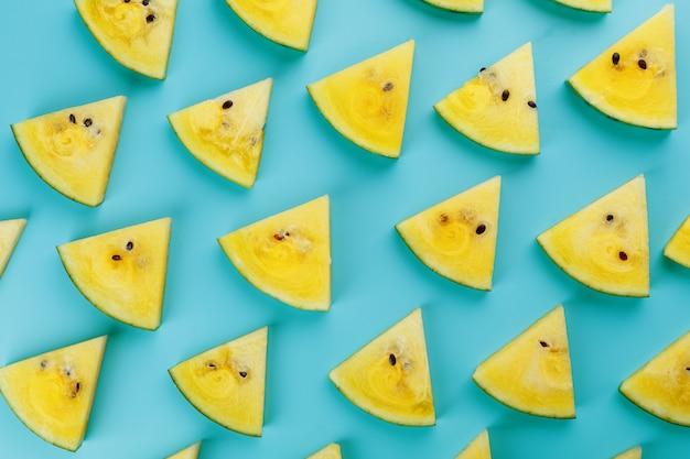 Motif de tranches de tranches fraîches de melon d'eau rouge et jaune sur un bleu. vue de dessus
