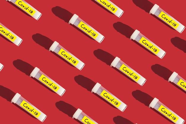 Motif sur un tube de fond rouge avec traitement pandémique du vaccin contre le coronavirus