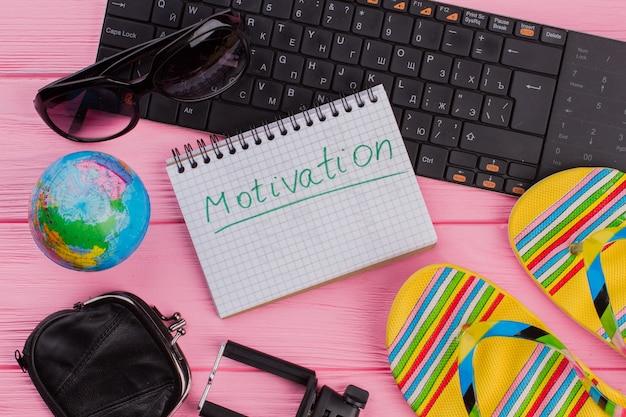 Motivation sur ordinateur portable avec portefeuille de lunettes d'accessoires de voyageur pour femme et tongs sur fond de table rose.globe et clavier noir.
