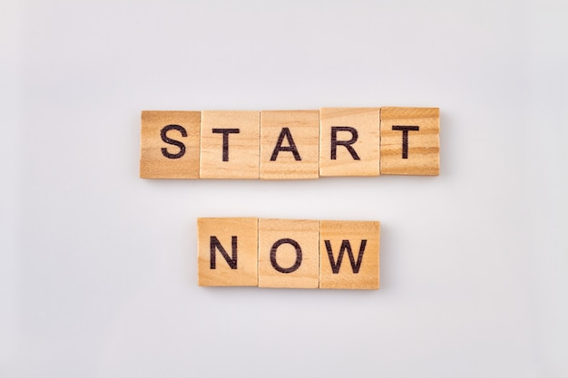 Motivation pour le travail. commencez maintenant à partir de blocs de lettres en bois sur fond blanc.