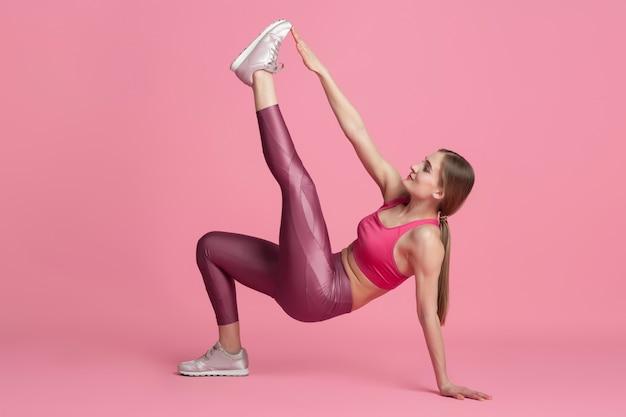Motivé. belle jeune athlète féminine pratiquant, portrait rose monochrome. entraînement de modèle caucasien en forme sportive. musculation, mode de vie sain, concept de beauté et d'action.
