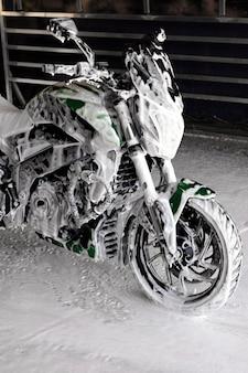 Moto au lavage de voiture dans le savon