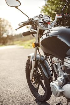 Moto brillante noire sur la route au-dessus d'un fond de nature