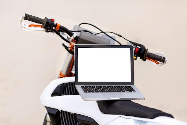 Moto élégante avec ordinateur portable sur le dessus dans le désert