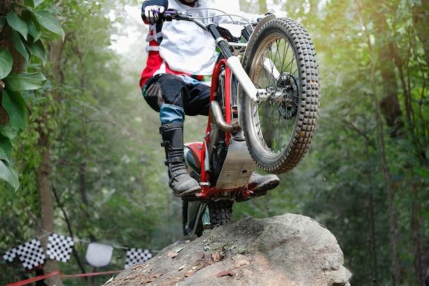 La moto des essais saute par-dessus les rochers