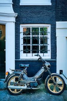 Moto garée près de la vieille maison dans la rue d'amsterdam