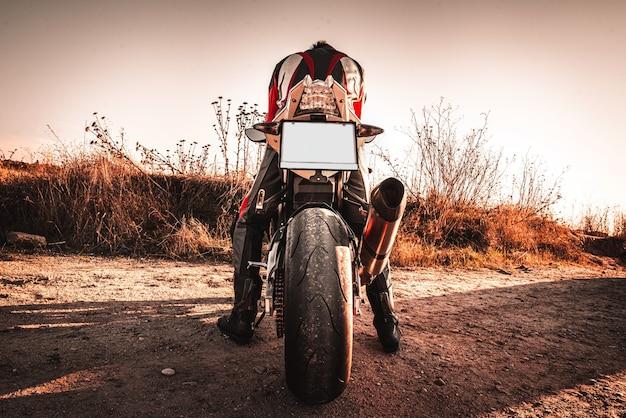 Moto de grosse cylindrée avec un motard sur le dos debout sur la route non goudronnée sous un ciel clair