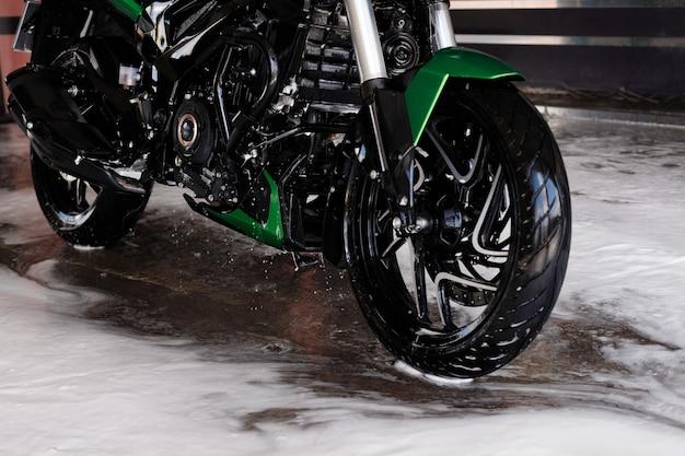 Moto en mousse au gros plan de lavage de voiture dans l'eau