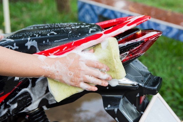 Moto propre, main féminine avec une éponge en mousse jaune lavant une moto.