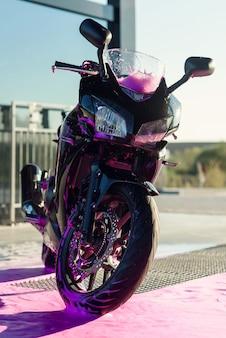 Moto de sport élégante avec de la mousse sur le lave-auto en libre-service au lever du soleil.