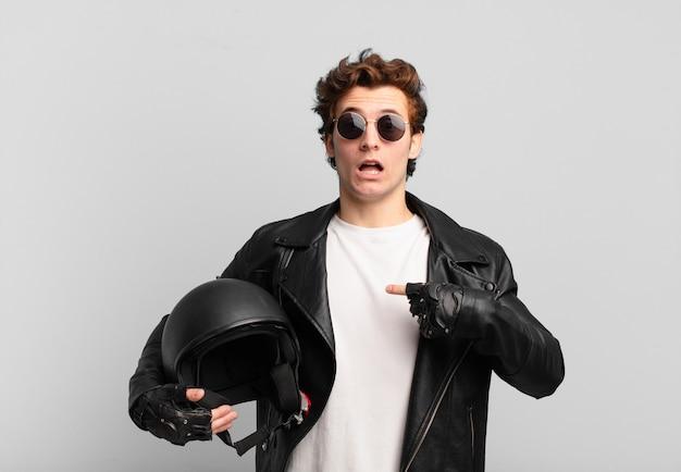 Motocycliste garçon à choqué et surpris avec la bouche grande ouverte, pointant vers soi