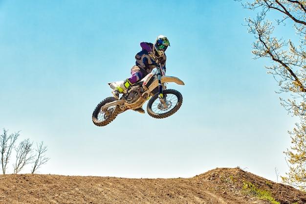 Motocycliste de saut de moto de sports extrêmes fait un saut extrême contre le ciel
